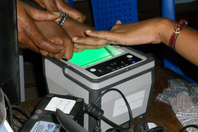 An individual records fingerprints as part of the biometric data collection for Aadhaar | Commons