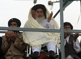 Head of the Tehreek-i-Labaik Yah Rasool Allah Pakistan (TLYRAP) religious group Khadim Hussain Rizvi (C), offers Friday prayers on a blocked flyover bridge