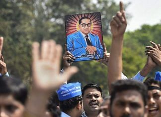 Members of Dalit community display a portrait of Bhim Rao Ambedkar during 'Bharat Bandh' in New Delhi | PTI