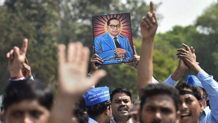 Members of Dalit community display a portrait of Bhim Rao Ambedkar during 'Bharat Bandh' in New Delhi | PTI