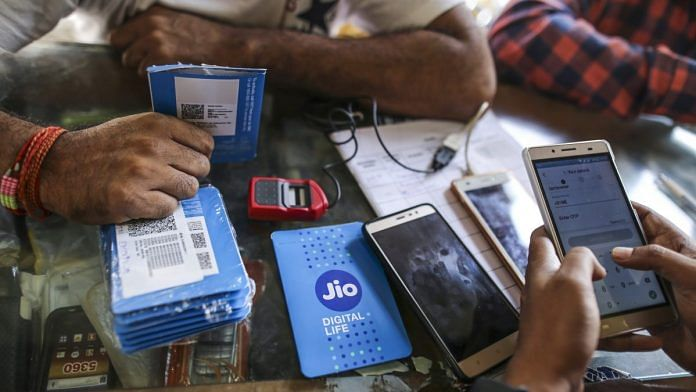 A customer holds a SIM card packet while waiting to connect his mobile phone to the carrier Reliance Jio | Dhiraj Singh/Bloomberg