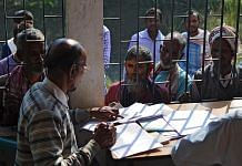 People wait to check their names on the first draft of the National Register of Citizens (NRC) in Assam