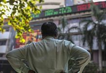A man stands in front of an electronic ticker board showing stock information figures outside the Bombay Stock Exchange (BSE) in Mumbai | Dhiraj Singh | Bloomberg