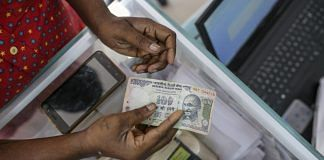 A customer holds Indian one hundred rupee banknote in India | Dhiraj Singh/Bloomberg