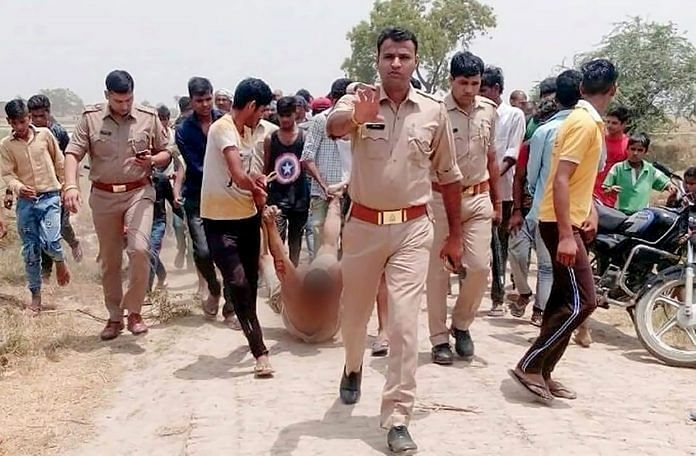 An injured man lynched fpr alleged cow slaughter is being dragged by locals in the presence of police personnel in Hapur ~ PTI