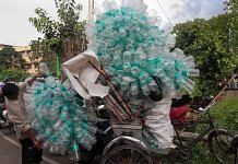 A worker loads a rickshaw with empty plastic water bottles | PTI