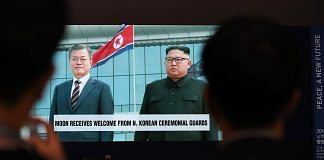 A screen showing a broadcast, featuring South Korean President Moon Jae-in meeting North Korean leader Kim Jong-un | Bloomberg