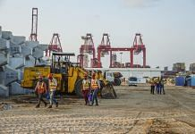 Workers walk past excavators at the site of Colombo Port City, developed by China Harbour Engineering Co