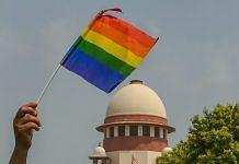 An activist waves a LGBT pride flag after the Supreme Court verdict | Kamal Kishore/PTI