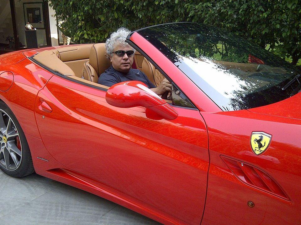 Suhel Seth in a red Ferrari