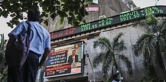 A man looks up at an electronic ticker board that indicates stock figures at the Bombay Stock Exchange (BSE)