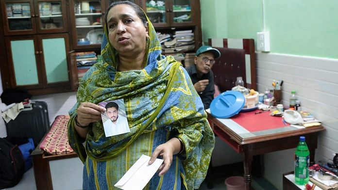 Najeeb's mother Fatima Nafees and his father Naseer Ahmed show a photograph of their missing son | Manisha Mondal / ThePrint