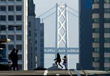Pedestrians cross the street in front of the Oakland-San Francisco Bay Bridge in California   David Paul Morris/Bloomberg
