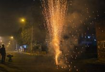 Revelers watch a firework during Diwali celebrations in Delhi | Prashanth Vishwanathan/Bloomberg