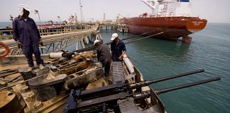 Iraqi oil workers secure the ropes of an oil tanker at Iraq's Al Basra oil terminal in the Northern Arabian Gulf