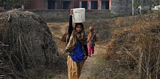 Women carry vessels of drinking water along a track in Haryana | Anindito Mukherjee/Bloomberg