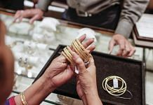 A woman tries on gold bangles at a jewellery store | Representational image | Photo: Dhiraj Singh | Bloomberg