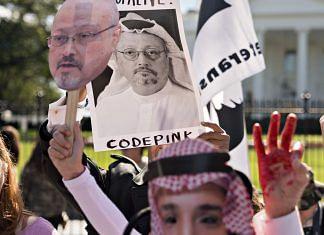 Protesters hold photographs of journalist Jamal Khashoggi outside the White House in Washington, D.C. 