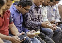 Passengers use smartphones at Mumbai Central railway station | Dhiraj Singh/Bloomberg