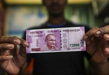 A man holds a Rs 2000 banknote | Dhiraj Singh/Bloomberg