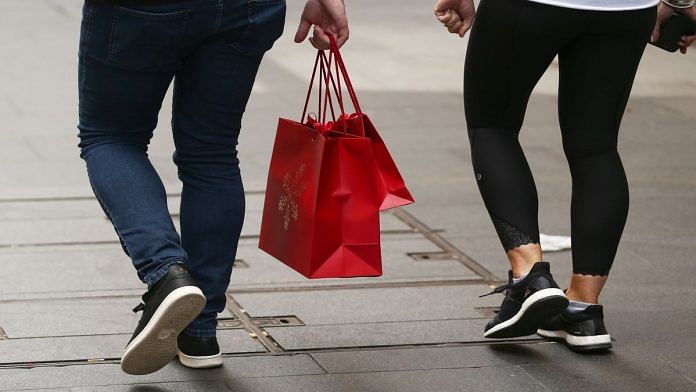 A shopper carries red shopping bags in Sydney, Australia | Brendon Thorne/Bloomberg