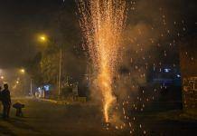 Revelers watch a firework during Diwali celebrations in Delhi