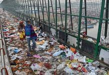 Pedestrians walk over plastic bags scattered on the pavement along Geeta Colony Setu over the River Yamuna, in New Delhi