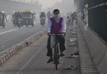 A cyclist protects himself with a handkerchief against air-pollution as he rides through smog, at ITO Bridge in New Delhi