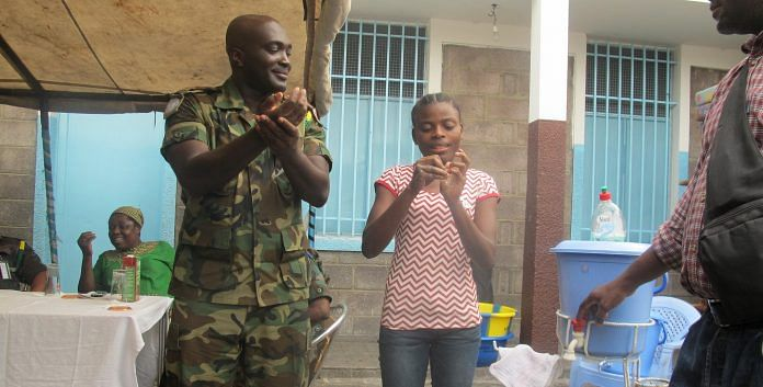 Fighting against Ebola in DR Congo: A MONUSCO Ghanaian peacekeeper showing a young girl how to properly wash hands