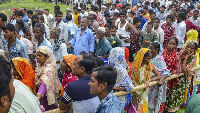 People wait to check their names on the final draft of the Assam's National Register of Citizens