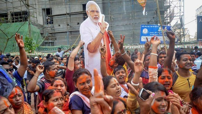 BJP supporters hold up a placard of PM Narendra Modi in in Agartala| PTI