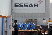 Signage for Essar Steel Ltd. is displayed as workers load items onto a truck at the company's Pune Facility in Maharashtra
