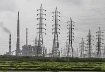 Smoke rises from a chimney as electricity pylons stand at the Tata Power Co. Trombay Thermal Power Station | Bloomberg