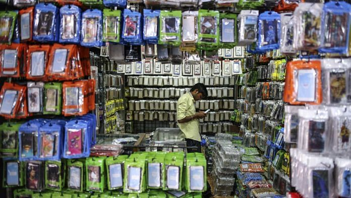 A vendor uses a smartphone at a wholesale stall selling mobile phone accessories (Representational image)