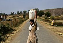 A woman carrying water on her head crosses a road in Bhopal District | Anindito Mukherjee/Bloomberg