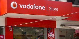 Customers talk on mobile phones outside a Vodafone India Ltd. store | ThePrint,in