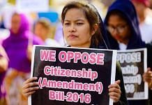 A girl holds placard during a protest against citizenship Act