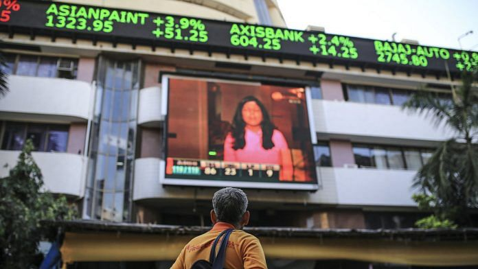 A man stands outside the Bombay Stock Exchange building in Mumbai | Dhiraj Singh/Bloomberg