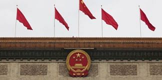 The Chinese national emblem and flags are displayed above the Great Hall of the People in Beijing, China (representational image) | Photo: Giulia Marchi | Bloomberg
