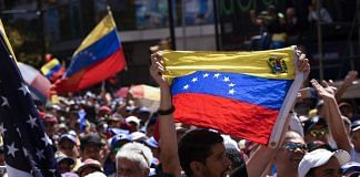 Opposition supporters wave Venezuelan flags during a rally against Nicolas Maduro, Venezuela's president | Carlos Becerra/Bloomberg