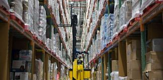 A worker uses a forklift to remove a pallet of goods from a storage rack in an aisle at the Amazon Inc. fulfillment center in Bengaluru