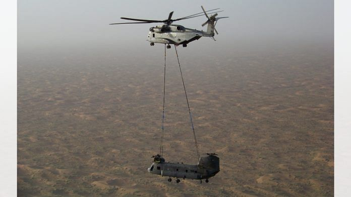 An Mi-26 helicopter airlifting a Chinook helicopter