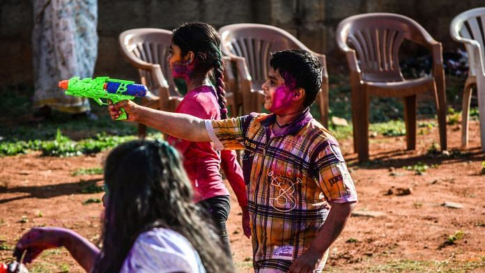Kids squit water from a toy gun during Holi | Flickr