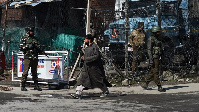 Security personnel guard a street during a strike call given by traders in protest against the extension of Central laws to Jammu and Kashmir and ban on Jamaat-e-Islami