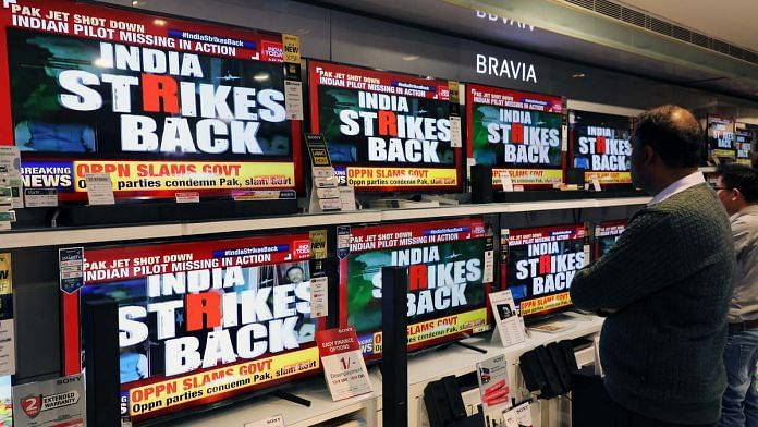 A man watches a television news report on the confrontation between Indian and Pakistani fighter jets in an electronics store in New Delhi
