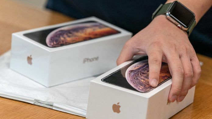 An employee holds a box of the Apple Inc. iPhone XS at an Apple store during its launch in Hong Kong, China