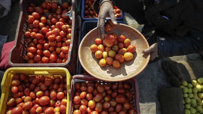 A vendor fills a bowl with tomatoes at a vegetable market