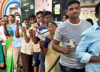 Voters stand in a queue to cast their vote at a polling station in Mumbai