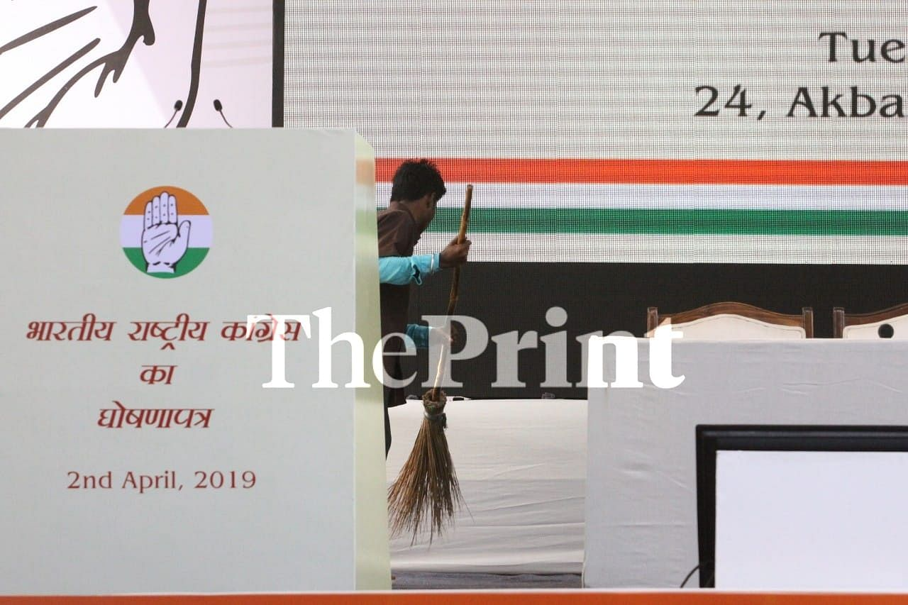 A party supporter gives a final brush to the stage before the manifesto launch at AICC headquarters | Praveen Jain/ThePrint