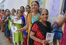 Women voters queue up to cast their votes at a polling station